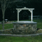 """This faux wishing well was created as a """"dry well"""" for all drainage systems on the property such as driveway drainage and gutters to release into. Sinopoli Contractors designed the feature to make it aesthetically appealing while structurally functional. Landscaping was added to enhance the overall appearance of the structure and cobblestone curbing adds a finishing touch."""
