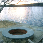 Close up photo of lakeside patio with a custom-made fire pit made of blue stone and natural fieldstone with a fire brick interior and a custom fabricated blue stone top. Project included excavation, drainage, final grading and masonry work. (Photo 2 of 2)