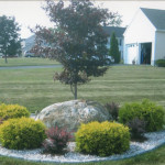 Designed and installed landscape feature incorporating a native boulder surrounded by plants and landscaping material and framed with cobblestone accents. Decorative stone was used instead of mulch to complement landscaping around home and to minimize maintenance. (Picture 2 of 3)