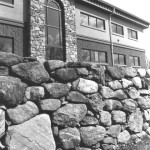 This arched entrance incorporates fieldstone in industrial design to soften the building's commercial appearance. The keystone in the arched window acts as a wedge and is integral to supporting the weight of the stone. The window glass was custom-made.