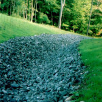 """After: To eliminate further erosion, a rip-rap swale was created to prevent further damage and enhance the landscape. Regrading followed and lawn was planted using """"Sinopoli seed""""."""