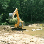 Using an excavator, a pond is nested in a stream with stepping stones added to ease crossing.