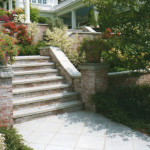 Brick work, retaining walls and cement steps all designed to complement home architecture and create decorative planting beds.