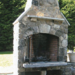 This custom exterior fireplace is an original design that includes native fieldstone and a limestone hearth, caps and mantel. The custom steel doors on the bottom cover a pizza oven and wood storage area.