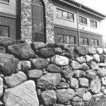 This arched entrance introduces fieldstone to industrial design to soften the commercial appearance. The keystone in the arched window acts as a wedge and is integral to supporting the weight of the stone. The window glass was custom-made.