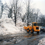 Stockpiling snow in an out of the way area to make room for more snow being delivered from space-constrained parking lots. Loaders, utility pick ups and dump trucks are engaged in the snow removal process.